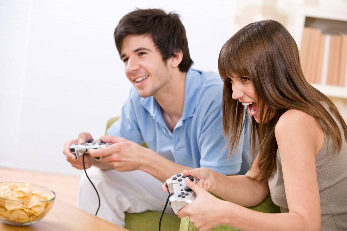 Mann und Frau spielen gemeinsam ein Videospiel mit Controllern in der Hand