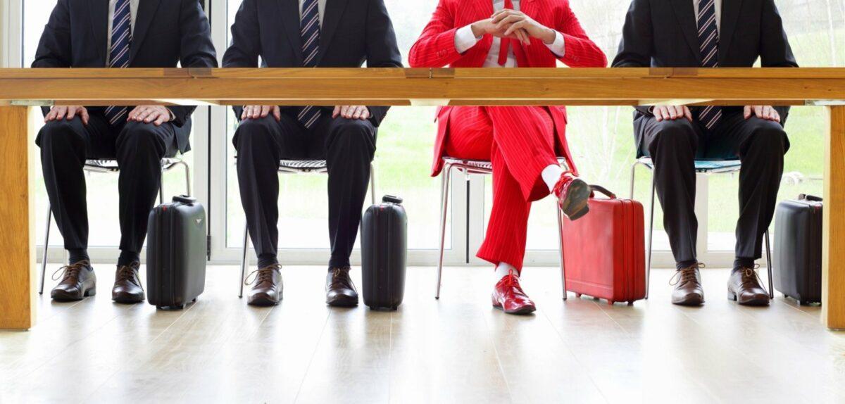 Menschen in Anzügen sitzen an einem Tisch