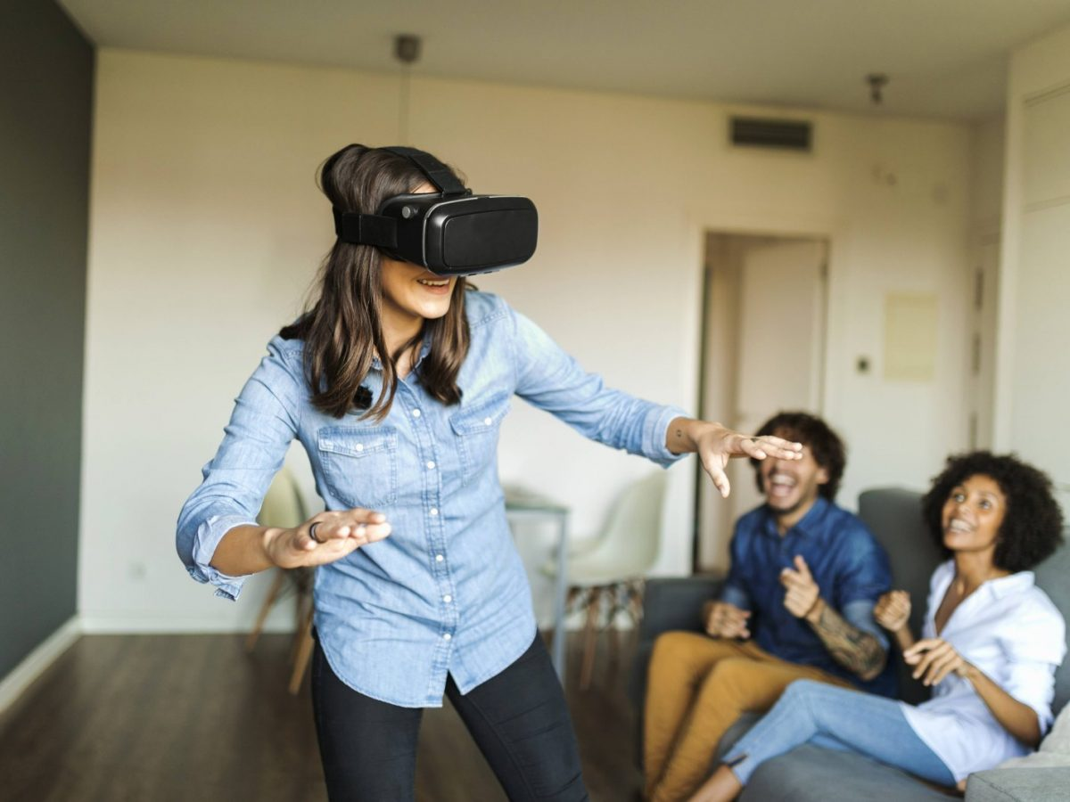 Frau mit einer VR-Brille und Freunden.