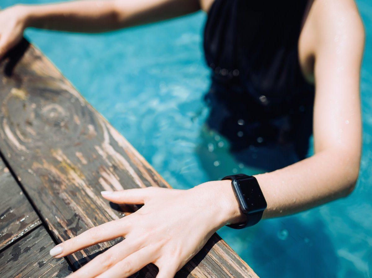 Hand mit Smartwatch am Arm am Beckenrand.