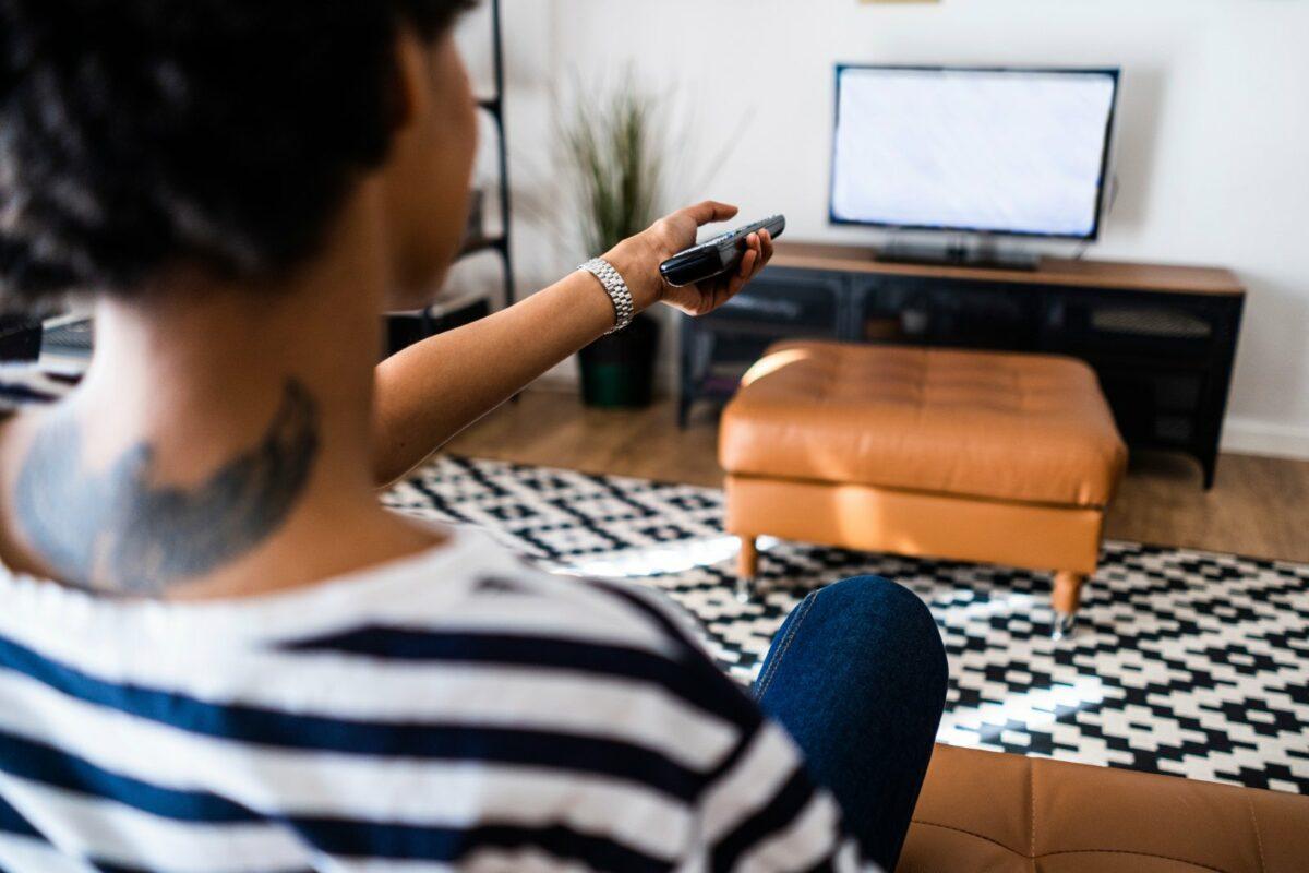 Frau schaltet Fernseher um