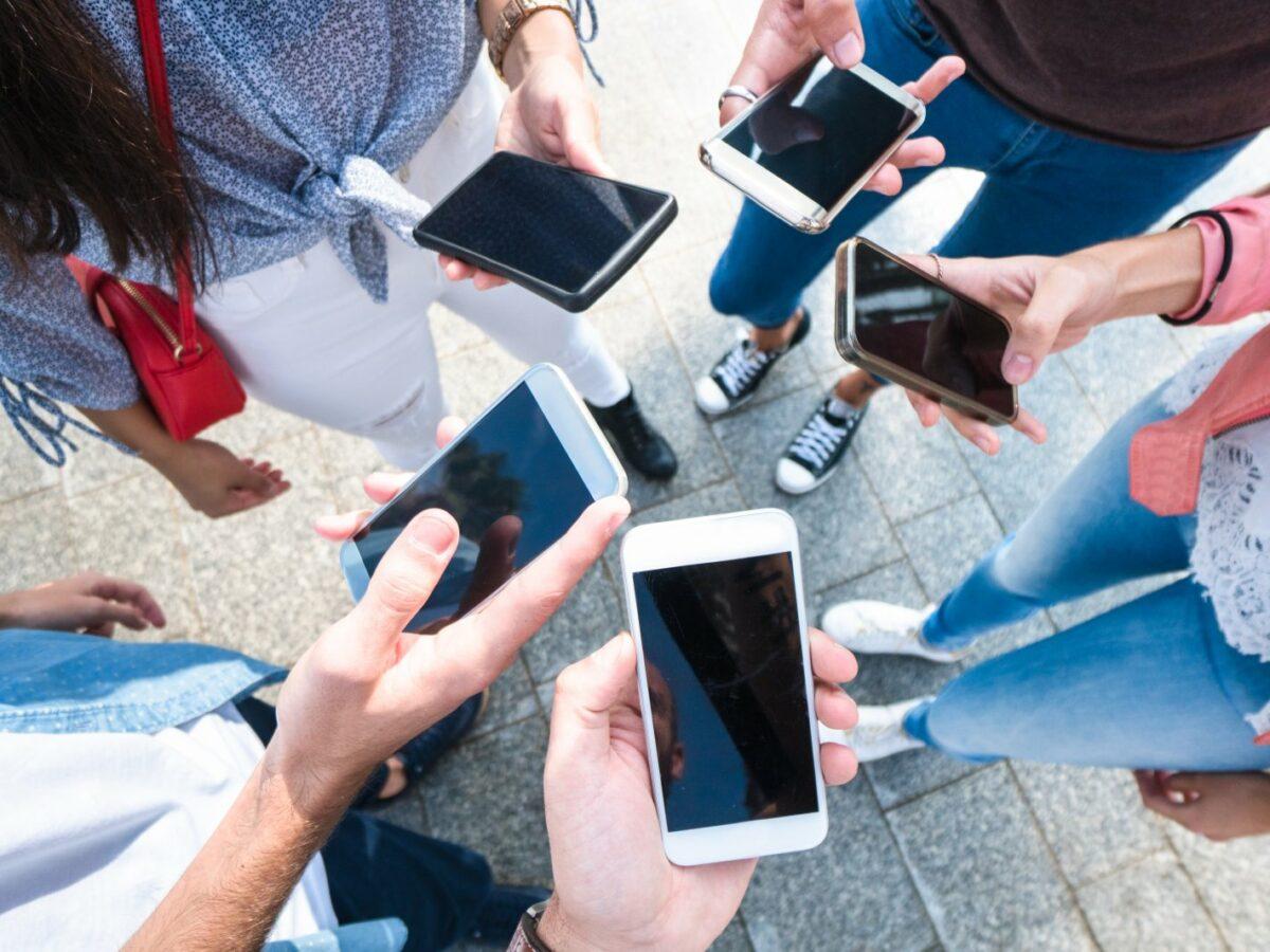 Menschenhände mit verschiedenen iPhones in der Hand.