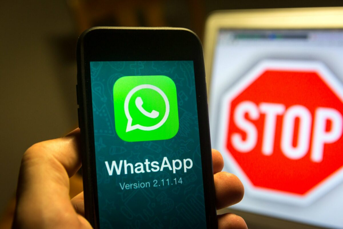 WhatsApp auf dem Handy und ein Stoppschild im Hintergrund