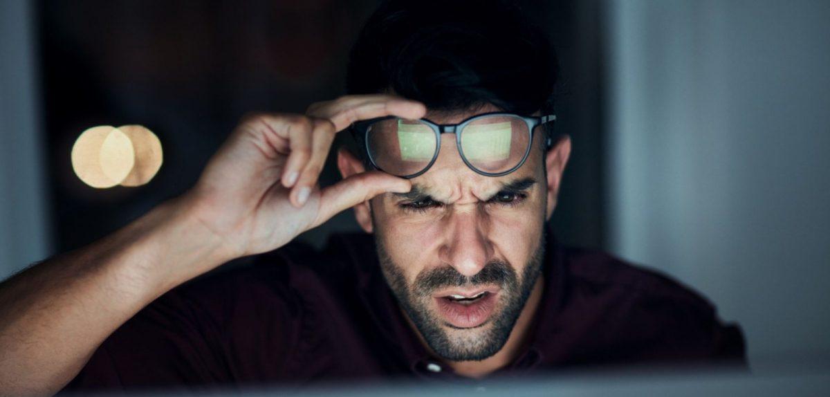 Mann blickt ungläubig auf seinen Monitor
