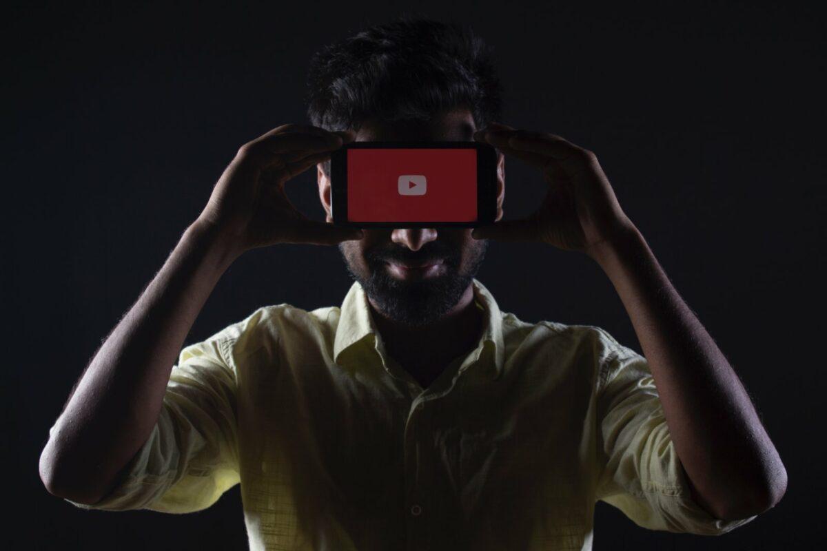 Person hält Handy vor dem Kopf