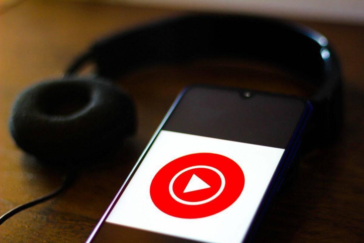 Handy mit YouTube App liegt neben Kopfhörern.