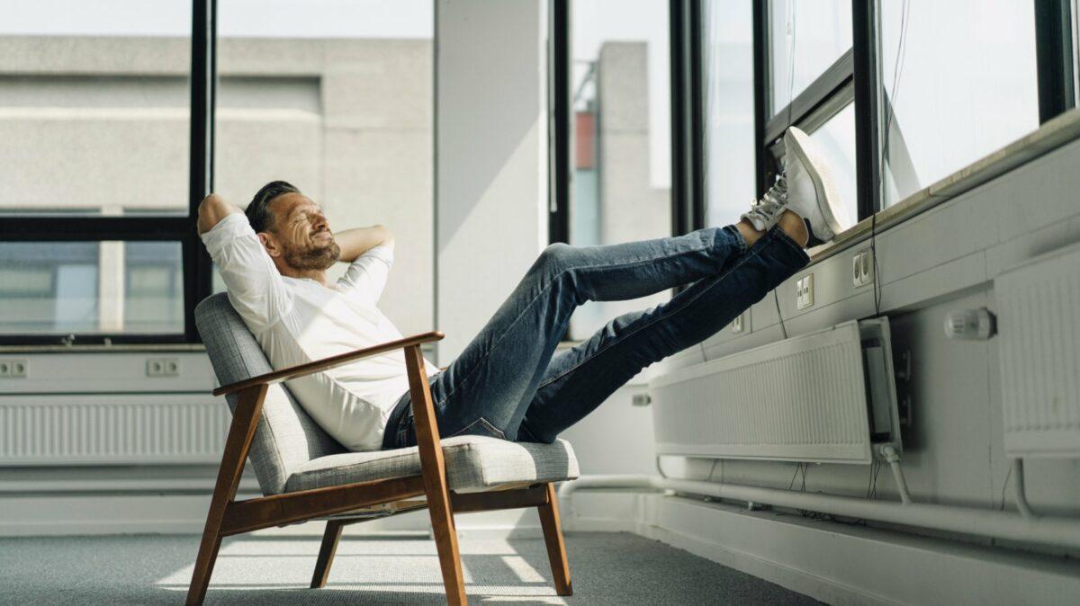 Mann entspannt auf dem Stuhl.