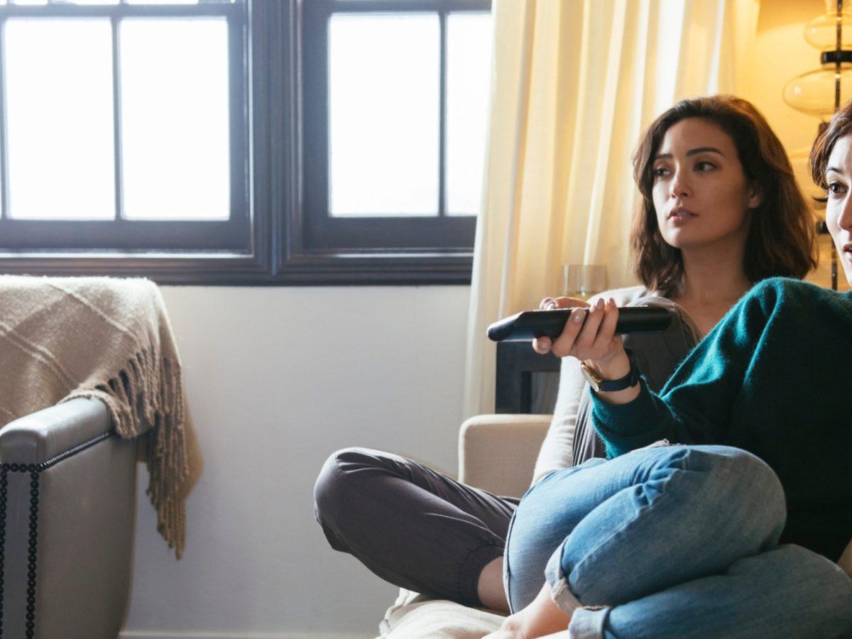Zwei junge Frauen sitzen auf dem Sofa und schauen Fernsehen