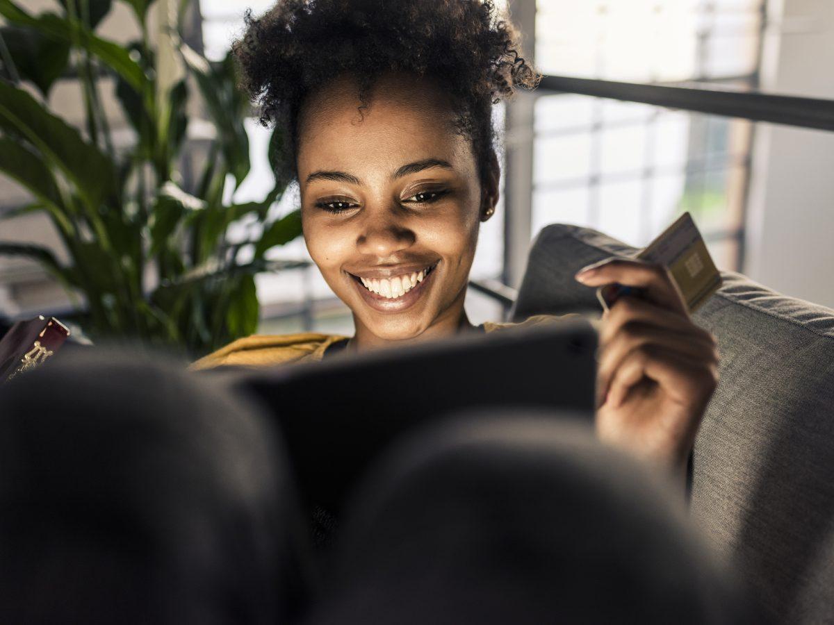 Eine Frau sitzt auf dem Sofa und schaut in ihren Laptop
