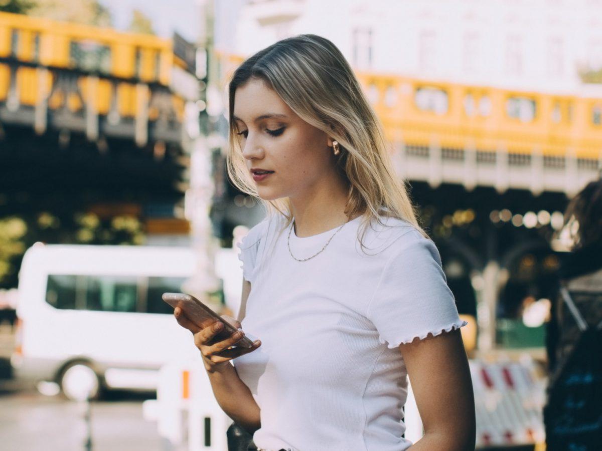Frau schaut auf ihr Smartphone in den Straßen Berlins