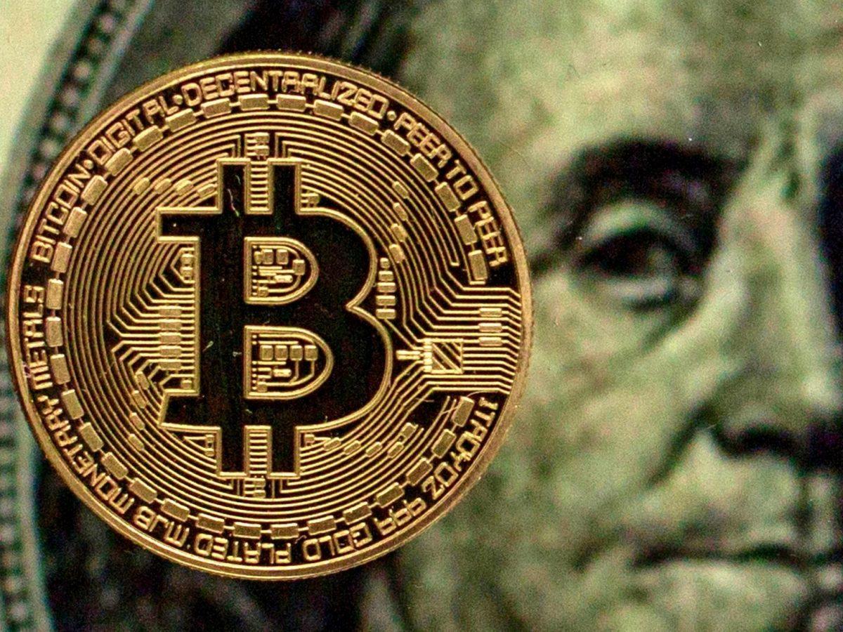 Bitcoin vor einem Dollar-Schein