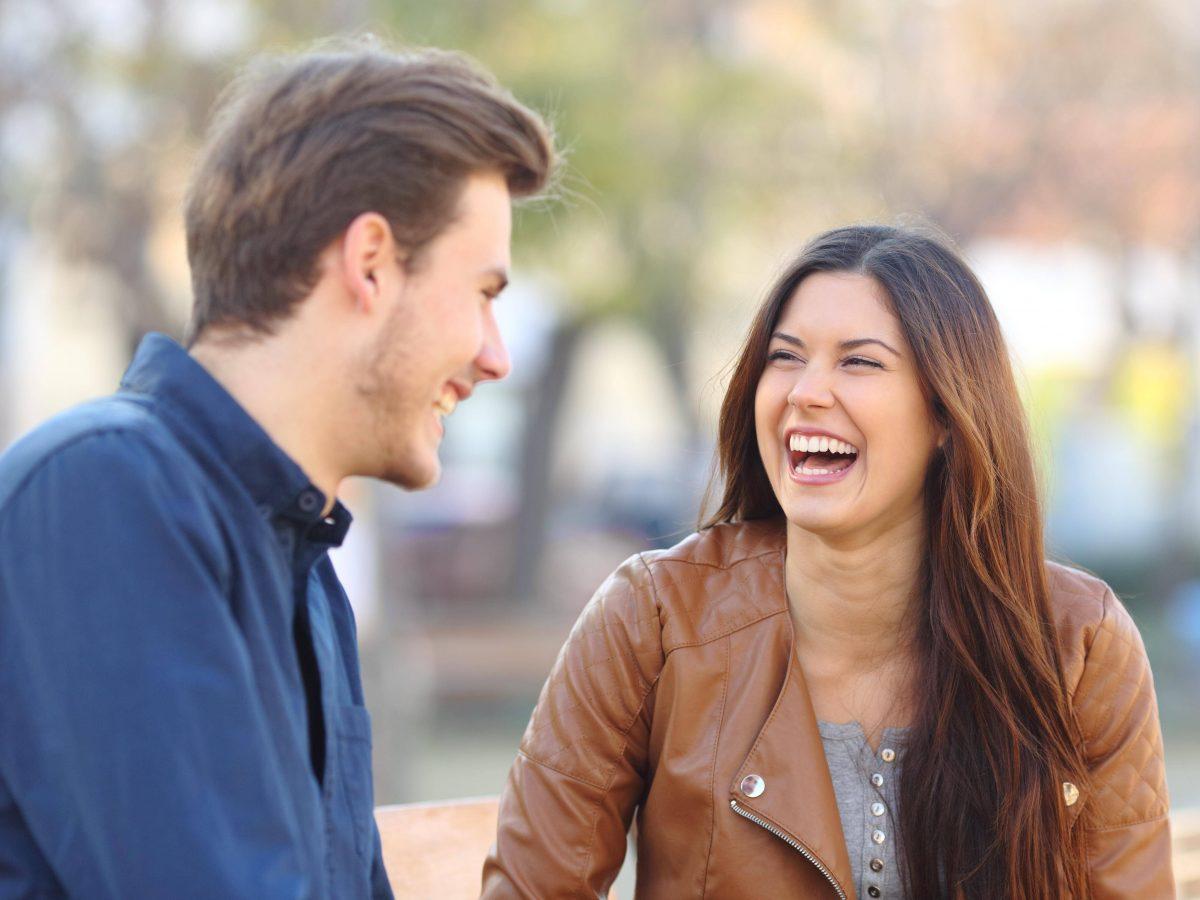 Mann und Frau lachen miteinander.