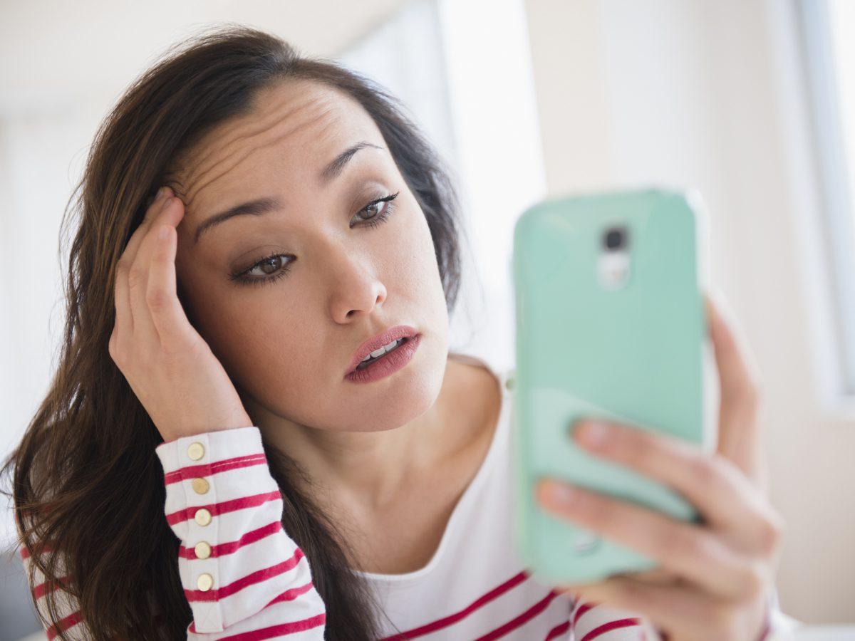 Frau gestresst am Handy