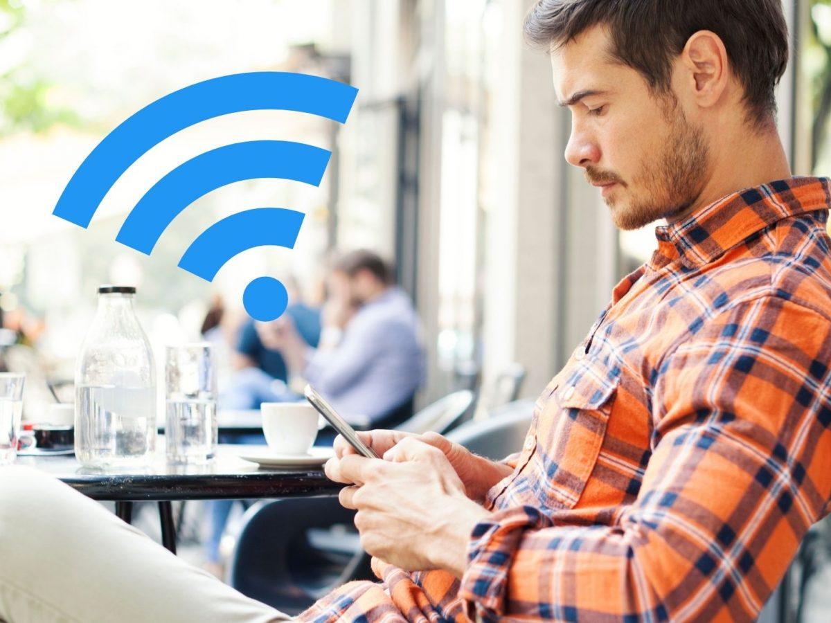 Mann im Café am Handy.