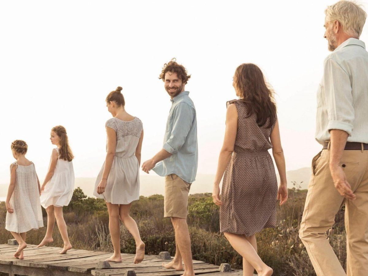 Menschen von jung bis alt laufen einen Uferweg entlang.