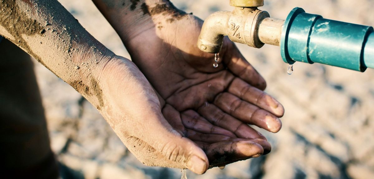 Trockene Hände unter einem Wasserhahn