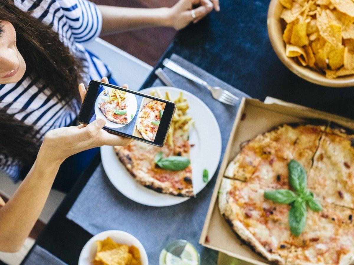 Frau fotografiert ihre Pizza auf dem Tisch.